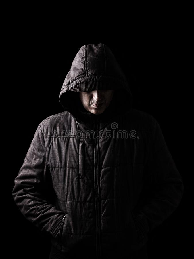 Scary and creepy caucasian or white man hiding in the shadows. With the face and identity hidden with the hood, and standing in the darkness. Low key, black stock images