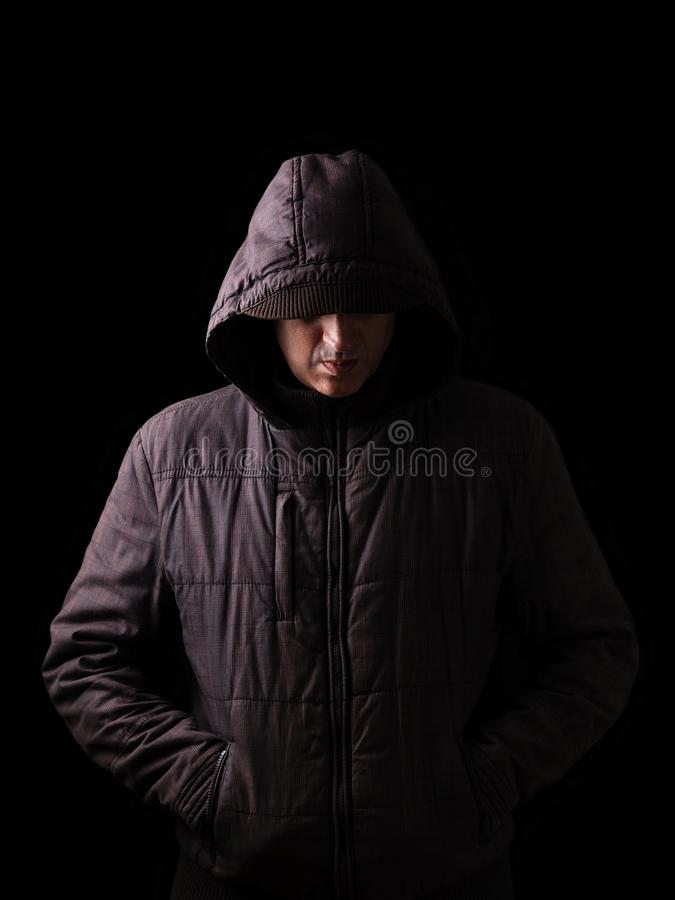 Scary and creepy caucasian or white man hiding in the shadows. With the face and identity hidden with the hood, and standing in the darkness. Low key, black stock photo