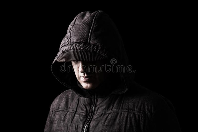 Scary and creepy caucasian or white man hiding in the shadows. With the face and identity hidden with the hood, and standing in the darkness. Low key, black stock photography
