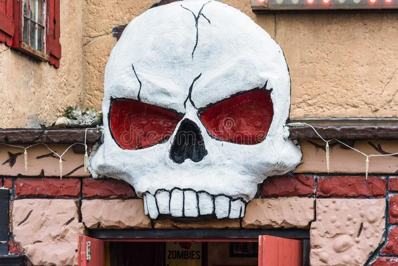 Creepy skull above the entrance of a haunted house royalty free stock photos