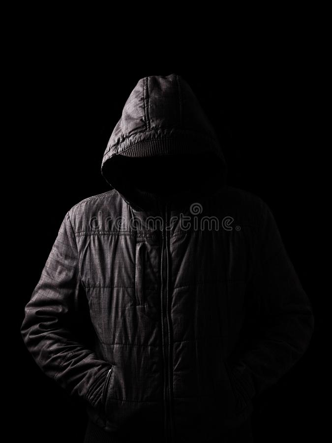 Scary and creepy man hiding in the shadows, with the face and identity hidden with the hood. And standing in the darkness. Low key, black background. Concept royalty free stock photography