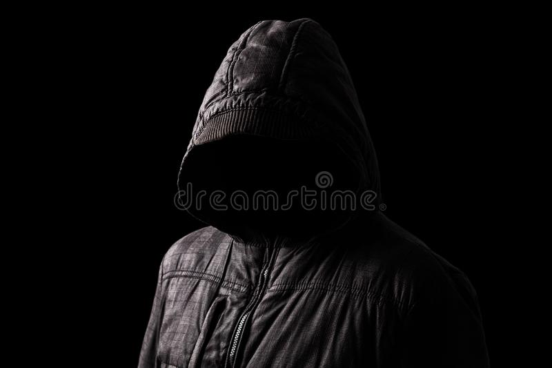 Scary and creepy man hiding in the shadows, with the face and identity hidden with the hood stock photo