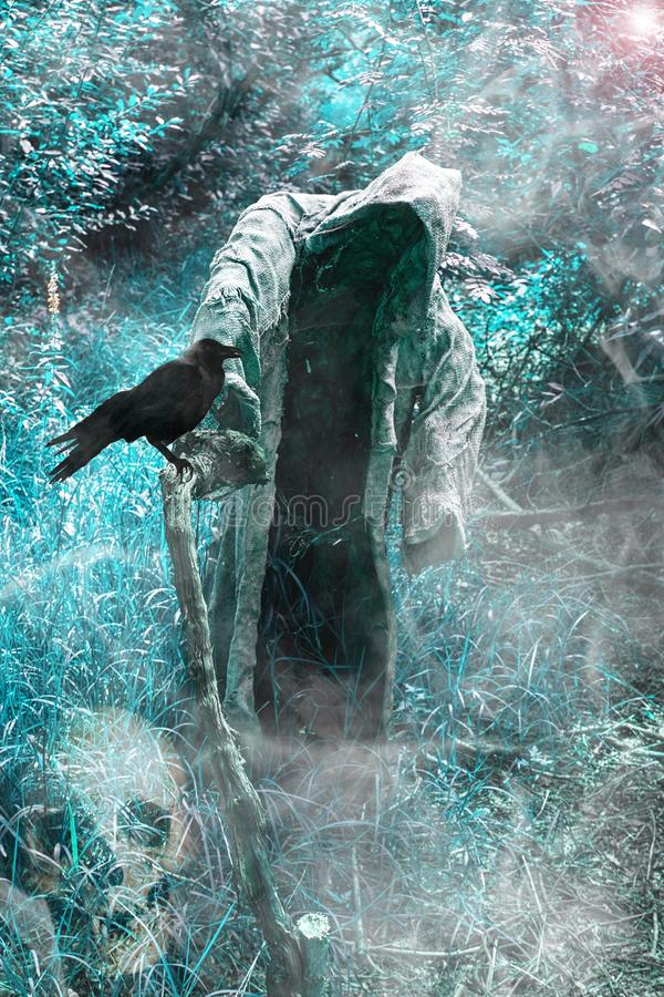 A grim reaper / ghost / witch in a long hood  in the middle of the dark woods. Scary and creepy person with hood standing in blue forest and holding stick of royalty free stock images