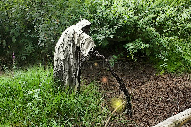 A grim reaper / ghost / witch in a long hood  in the middle of the woods in Furth im Wald Germany. Scary and creepy person with hood standing in forest and stock image