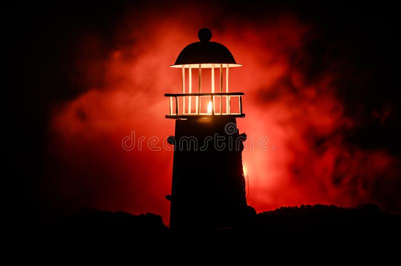 Scary dark ominous lighthouse behind a red fire background. Lighthouse at dusk/ Sunset Light House/ Light house at sunset. Decorat. Scary dark ominous lighthouse stock images