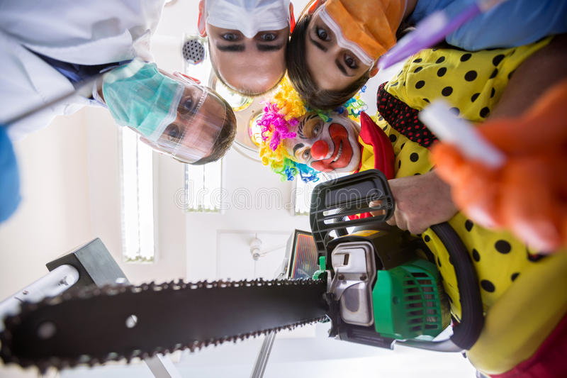 Scary delusion with dental team and clown in bottom view. Scary delusion with dental team and crazy clown with chainsaw in bottom view stock photos