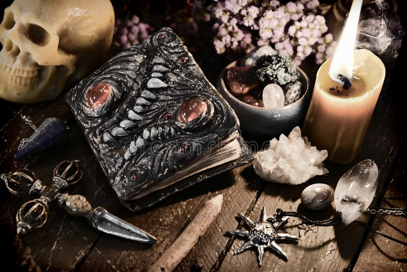Scary evil book with skull and burning candle stock images