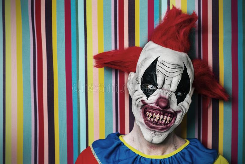 Scary evil clown in front of a circus tent. Closeup of a scary evil clown with red hair, white eyes, bloody teeth and a threatening look staring at the observer royalty free stock photos