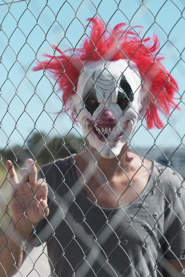 Scary evil clown outdoors. A scary evil clown looking with a threatening look through the wires of a fence stock photos