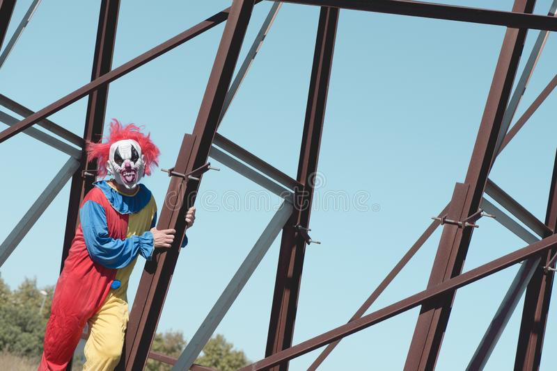 Scary evil clown sticking out his tongue outdoors. A scary evil clown, wearing a colorful yellow, red and blue costume outdoors, sticking out his tongue while stock photography