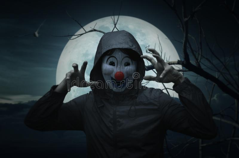 Scary evil clown wear jacket over bird, dead tree, moon and spooky cloudy sky royalty free stock photos