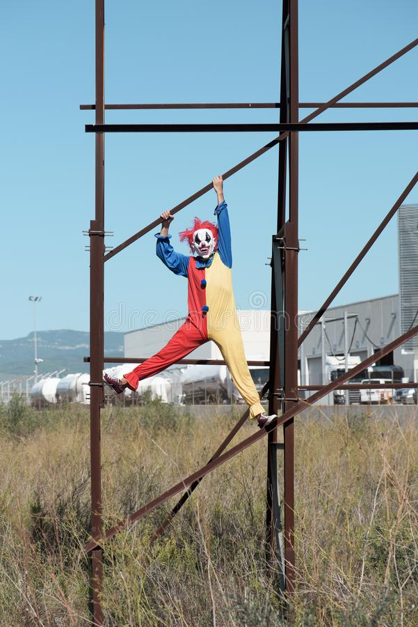 Scary evil clown outdoors. A scary evil clown wearing a colorful yellow, red and blue costume outdoors, hanging from the rusty structure of an abandoned stock photo