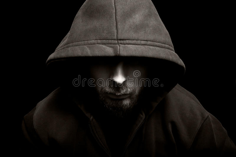 Scary evil man with hood in the dark royalty free stock image