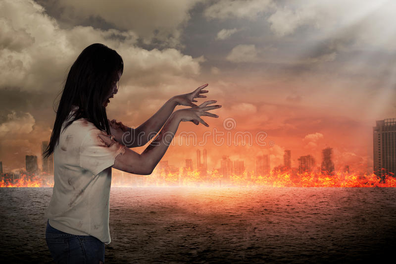 Scary female zombie with burning city background. Halloween concept stock photo