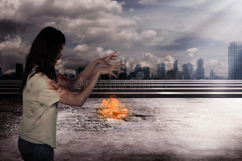 Scary female zombie with burning city background. Halloween concept royalty free stock image