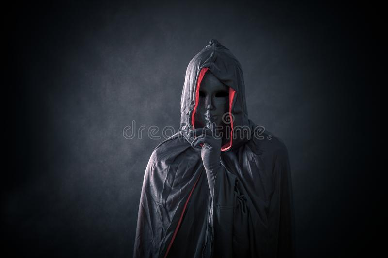 Scary figure with black mask in hooded cloak. In the darkness royalty free stock images