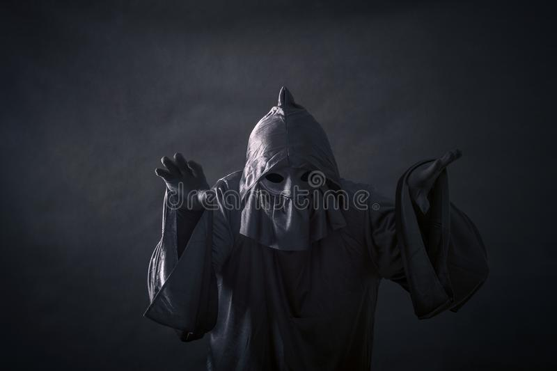 Scary figure in hooded cloak. In the darkness stock photos