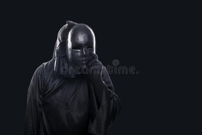 Scary figure in hooded cloak with mask in hand. On black background stock photos