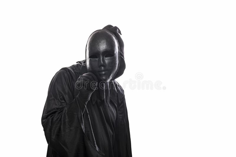 Scary figure in hooded cloak with mask in hand. Isolated on white background royalty free stock image