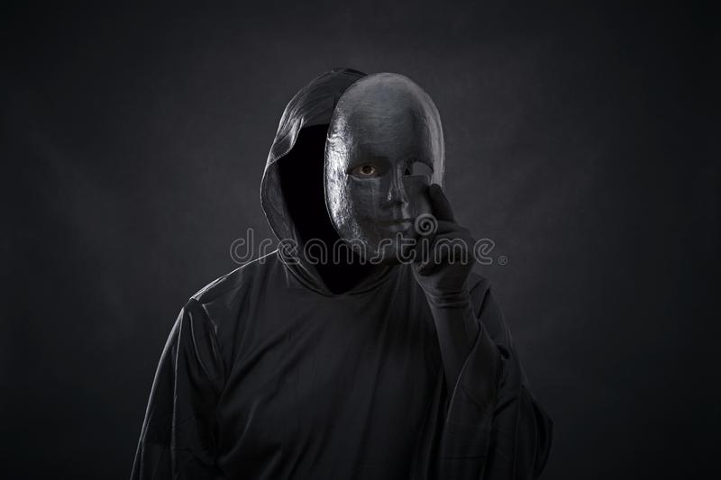 Scary figure in hooded cloak with mask in hand. Over dark background stock photo