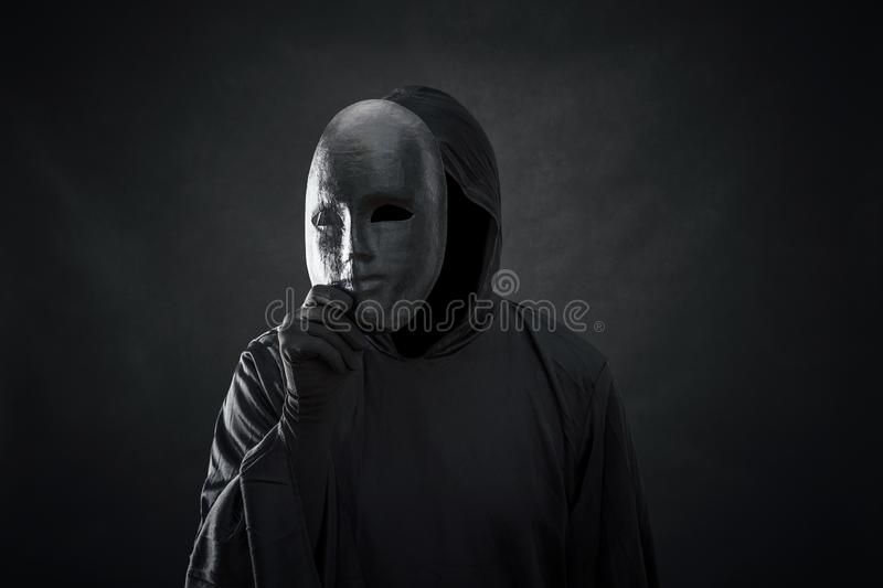 Scary figure in hooded cloak with mask in hand. Over dark background royalty free stock photos