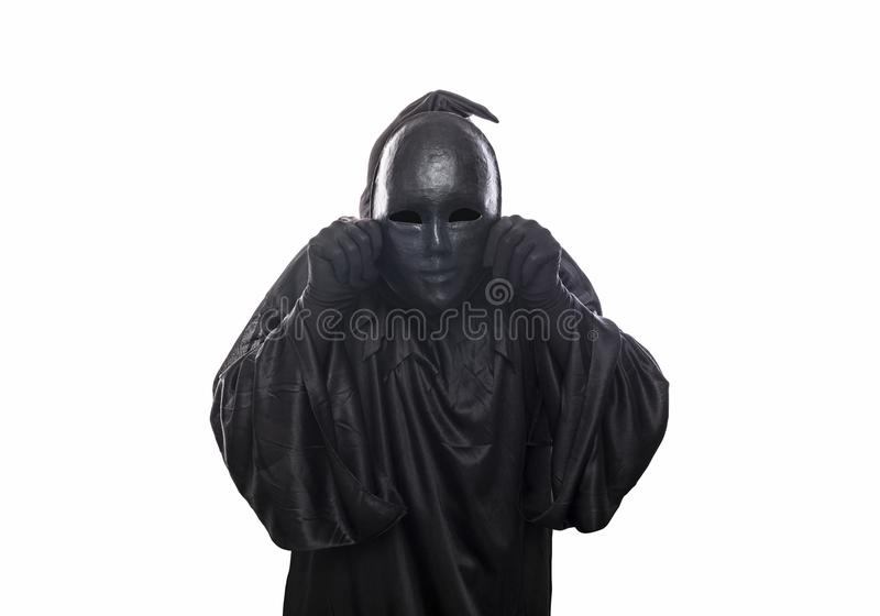 Scary figure in hooded cloak with mask in hands. Isolated on white background royalty free stock photography