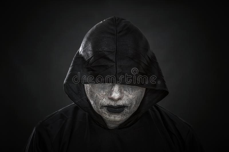 Scary figure in hooded cloak. Over dark background royalty free stock image