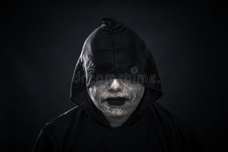 Scary figure in hooded cloak. Over dark background stock photo