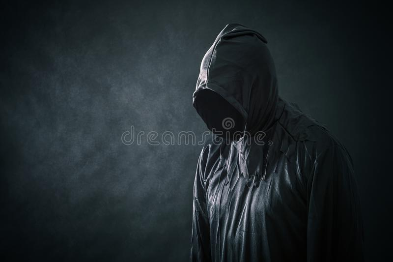 Scary figure in hooded cloak. In the darkness royalty free stock photos