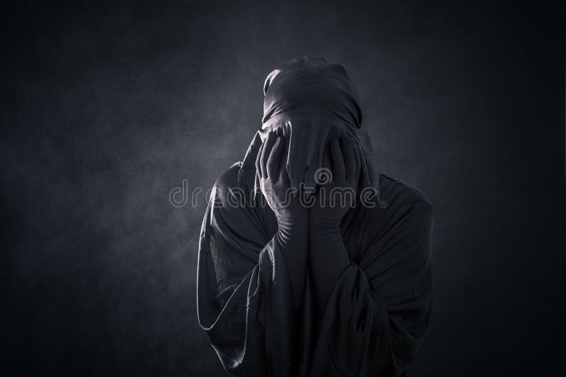 Scary figure in hooded cloak. In the darkness royalty free stock photo
