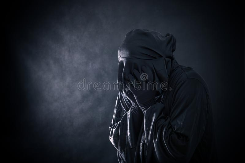 Scary figure in hooded cloak. In the darkness stock photography