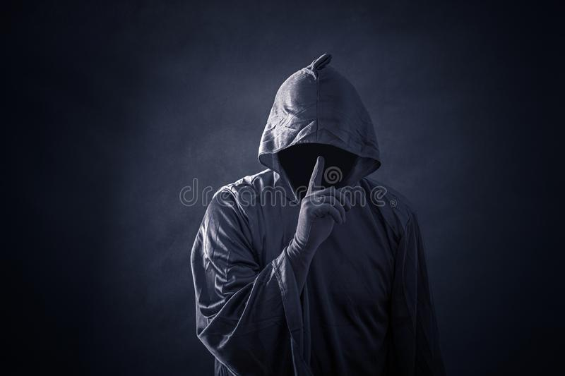 Scary figure in hooded cloak. In the darkness stock image