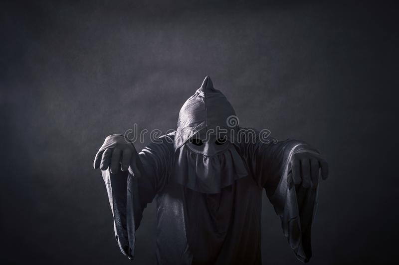 Scary figure in hooded cloak. In the darkness stock images
