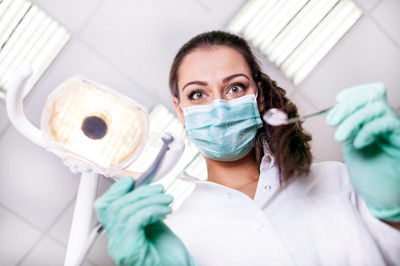scary and funny dentist working with a patient in protective work wear royalty free stock photography