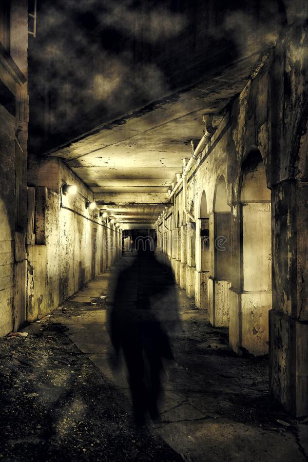A scary ghost walking in a dark city tunnel royalty free stock image