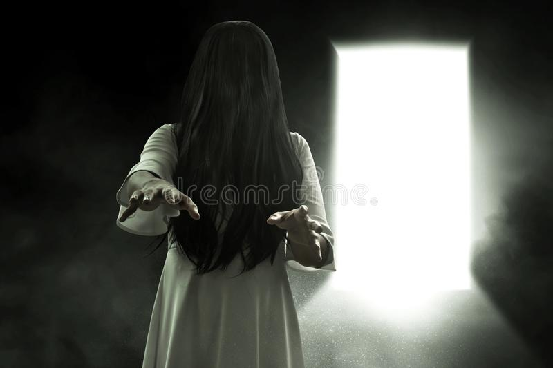 Scary ghost woman on dark background. S royalty free stock photo
