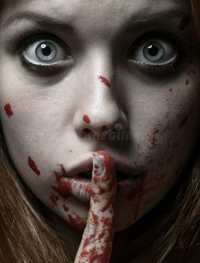 Scary Girl and Halloween theme: portrait of a crazy girl with a bloody face in the studio royalty free stock photography