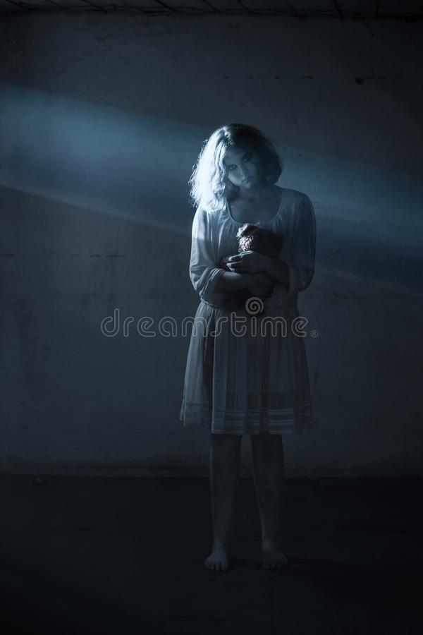 Scary girl in white dress from horror film in  room. The scary girl in white dress from horror film in  room stock photography