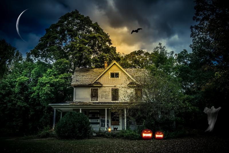 Scary Halloween House with Jack `O Lanterns on Halloween night royalty free stock images