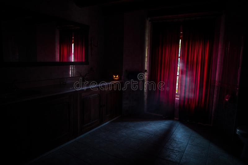 Scary Halloween pumpkin at scary dark room with red curtain at window or halloween pumpkin in night on room with horror window. Ha royalty free stock images
