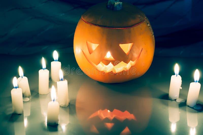 Scary Halloween pumpkin lantern ( jack-o'-lantern). With burning candles on a dark wooden background stock photo