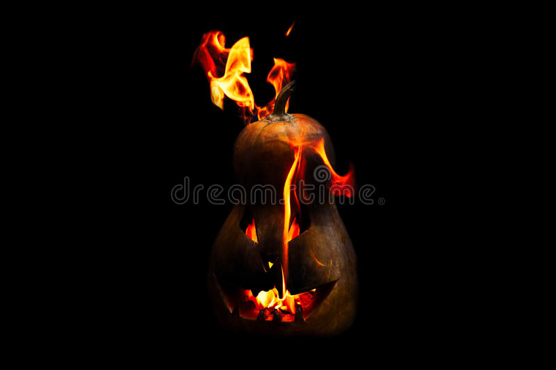 Scary Halloween pumpkin is spewing fire flame isolated on black. Background stock photography