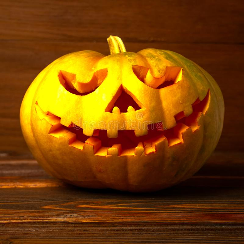 Scary Halloween pumpkin on wooden background . Scary glowing face trick or treat. Concept of halloween pumpkin on wooden stock photo