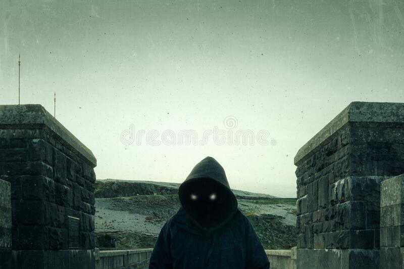 A scary, hooded figure with glowing evil eyes and blank black space where his face should be, standing on a road in the. Countryside in winter. With a vintage stock photography