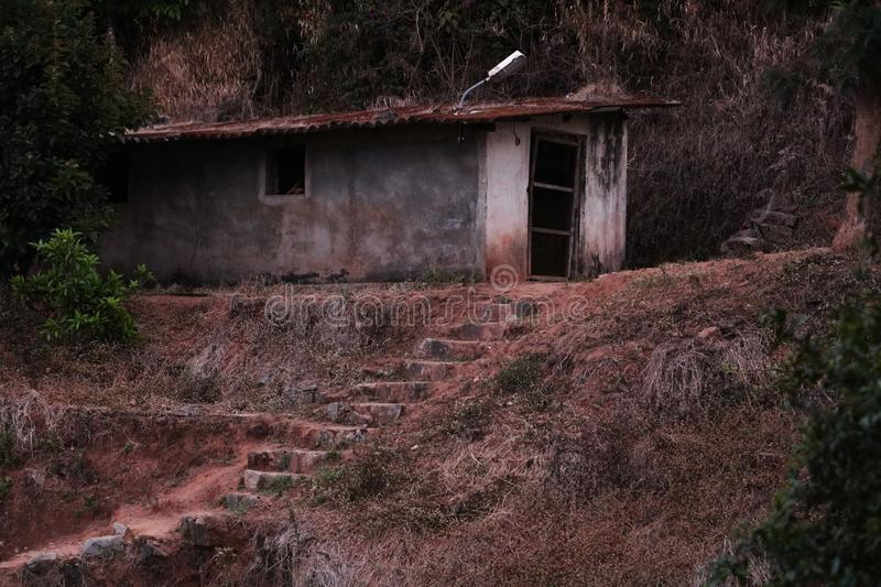Scary horror house at coorg. Old scary horror house with a rusted roof and door and unpaint house royalty free stock photo