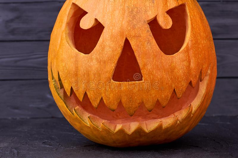 Scary Jack O Lantern face on dark wooden background. royalty free stock images