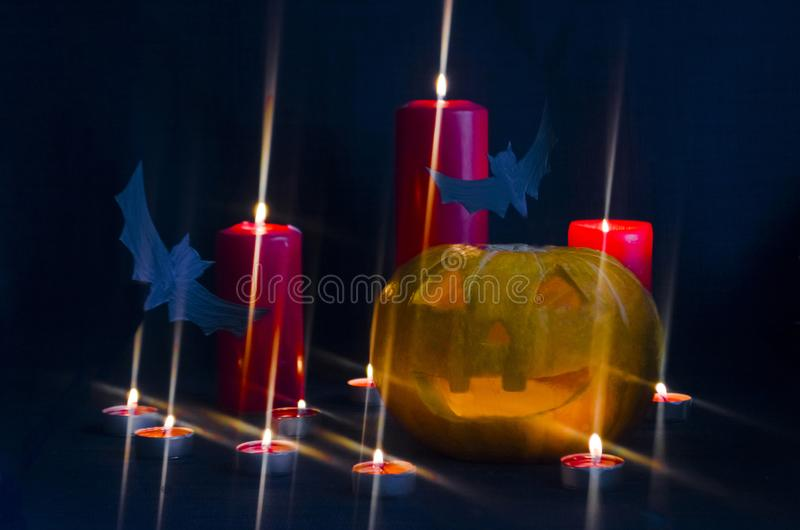 Scary Jack O Lantern halloween pumpkin with burning candle light inside with  bats. stock photography