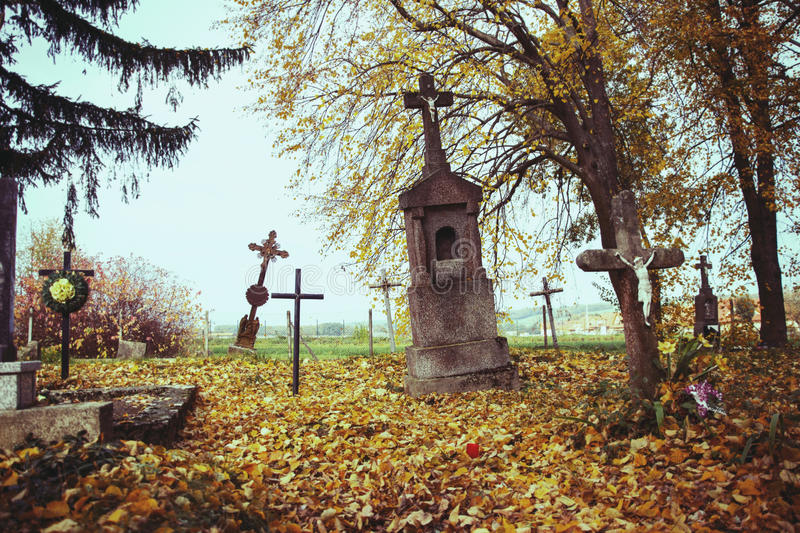 Scary leaning cross tomb stones in a foggy autumn scene in fall. Old creepy graves on cemetery in Slovakia. Spooky aged tombstones. On grave yard with trees stock photo