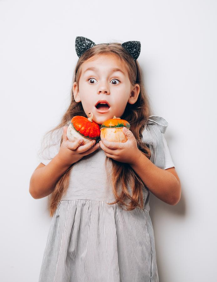 Scary little girl holding decorative pumpkins on white background stock photography