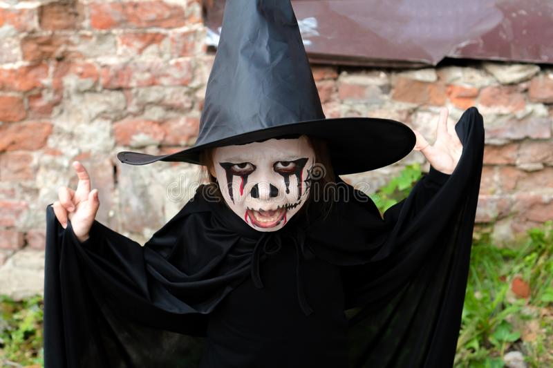 Scary little girl in a witch costume looking at camera with frightening expression on brick wall background. Scary little girl in a witch costume looking at stock photo